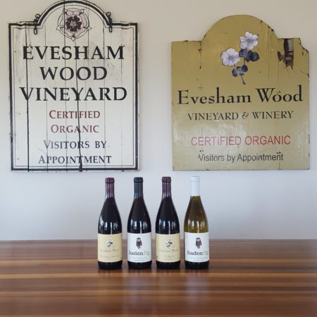 image: 4 bottles with vintage Evesham Wood winery signs behind.