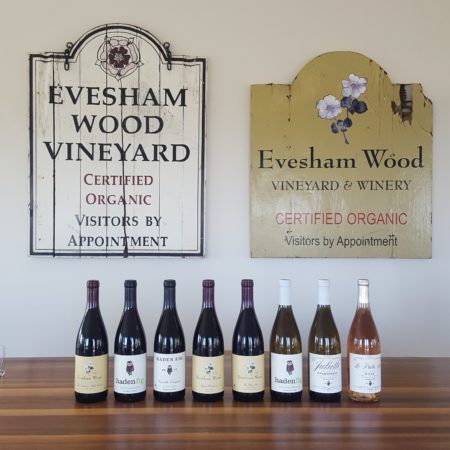 image: 8 bottles of wine on a table in front of two vintage Evesham Wood winery signs.
